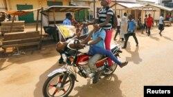 Quelques personnes se livrent à une acrobatie sur une moto près de la Mosquée Koudoukou à Bangui, en République centrafricaine, 30 novembre 2015.