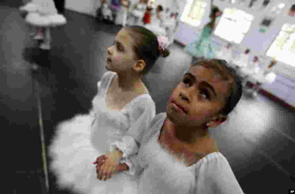 Deaf ballet student Raissa Goncalves (L) and her blind classmate Vitoria Rodrigues rehearse Don Quixote at the Association of Ballet and Arts for the Blind, in Sao Paulo November 19, 2011. The Association was founded by ballerina and physiotherapist Ferna