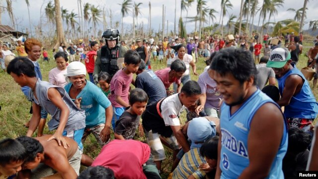 Survivors of typhoon Haiyan rush to grab fresh water delivered by a U.S. military helicopter to their isolated village north of Tacloban, Nov. 17, 2013.