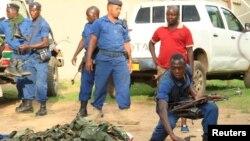 Polisi Burundi mengumpulkan senjata-senjata yang diperkirakan milik para pejuang pasca bentrokan di ibukota Bujumbura, Burundi (12/12).