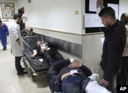 In this photo released by the Syrian official news agency SANA, Syrian injured men wait to receive medical treatments after they wounded in the main judicial building, which was attacked by a suicide bomber, in Damascus, Syria, March 15, 2017. Islamic State militants are believed to have been behind the attack.