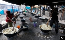 FILE: People prepare food made from cassava flour in a market in Nigeria.