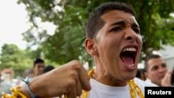 Estudiantes venezolanos rezan mientras se encadenas durante una protesta frente a la embajada de Cuba.