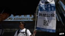 一名志愿者在街头举旗让公众意识到澳门非正式公投。(2014年8月24日)