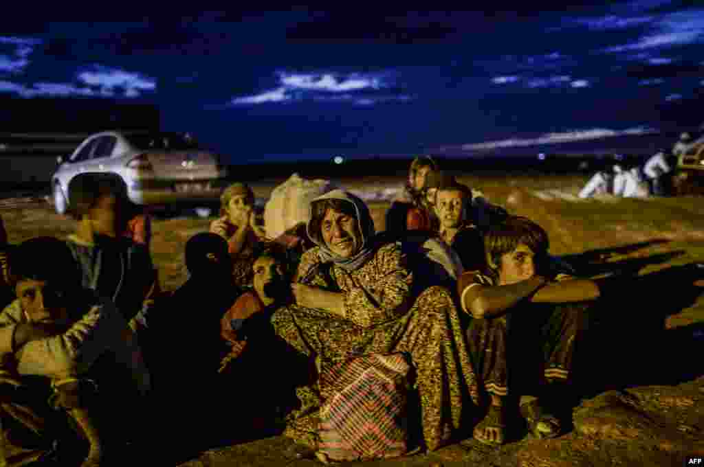 A Syrian Kurdish family waits after crossing the border between Syria and Turkey after several mortars hit both sides near the southeastern town of Suruc in Sanliurfa province, Sept. 29, 2014.