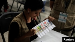 A woman takes part in a hand count of some of the votes cast in Honduras' recent presidential election in Tegucigalpa, Dec. 7, 2017.