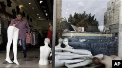 Israeli retailer cleans up after rocket from Gaza Strip lands nearby in Ashdod, March 13, 2012.