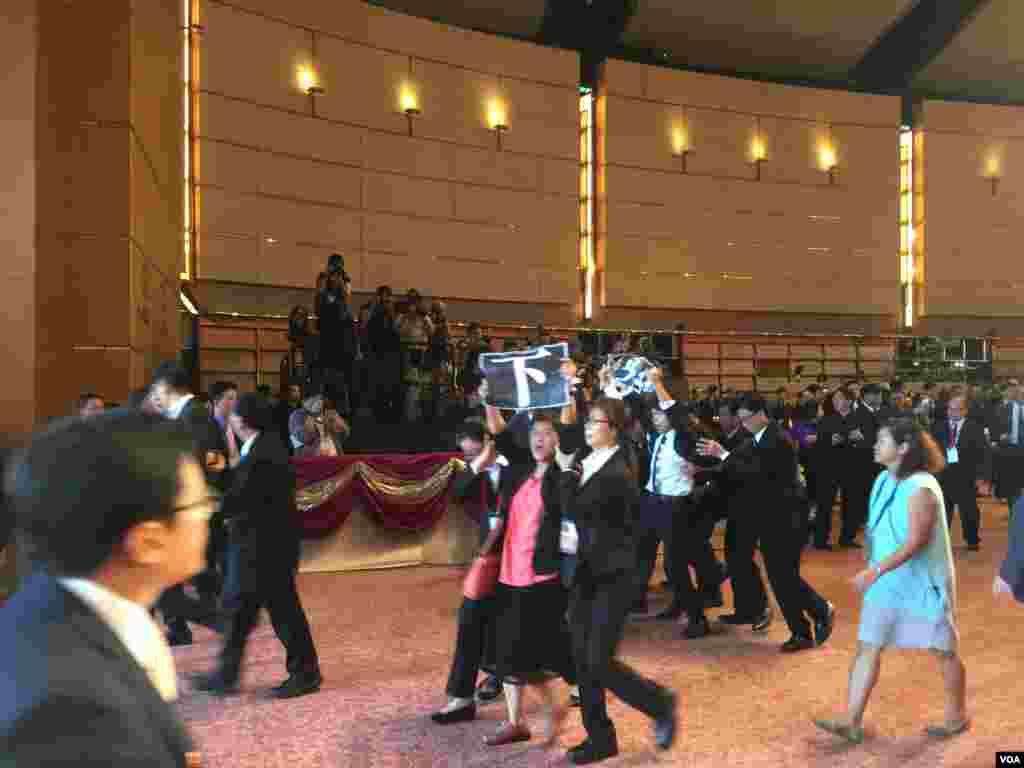香港特區政府星期六在會展中心舉辦國慶67週年大型酒會。在特首梁振英開始致辭後,參加酒會的多位候任民主黨立法會議員,舉起反梁標牌和單張,高喊梁振英下台的口號,被大批保安人員帶出會場。 (美國之音海彥拍攝)