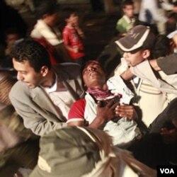 Demonstran anti pemerintah membawa rekannya yang terluka akibat penindakan oleh pasukan pemerintah di kota Taiz.