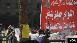 Seorang warga sedang beristirahat di dekat tendanya di lapangan Tahrir, Kairo. Aktifis menyerukan aksi massa sehari sebelum pemilu parlemen Mesir (27/11).