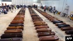 Lebih dari seratus peti jenazah para korban tenggelamnya kapal migran Afrika terlihat berderet di sebuah hangar bandara Lampedusa (5/10).
