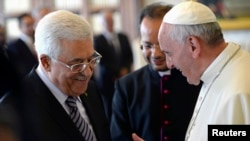 Pope Francis talks to Palestinian President Mahmoud Abbas (L) during a private audience in the pontiff library at the Vatican, Oct. 17, 2013.