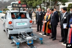 FILE - Then- President Lee Myung-bak looks at an electric vehicle while its test driving at the Korea Advanced Institute of Science and Technology or KAIST in Daejeon, South Korea, Friday, Feb. 27, 2009.