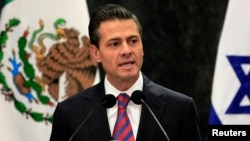 FILE - Mexico's President Enrique Pena Nieto gives a speech next to Israel's President Shimon Peres (not pictured) during a news conference at Los Pinos presidential residence in Mexico City, Nov. 27, 2013.