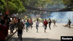 Protesters run from tear gas being fired by police during Irreecha, the thanks giving festival of the Oromo people in Bishoftu town of Oromia region, Ethiopia, Oct. 2, 2016.