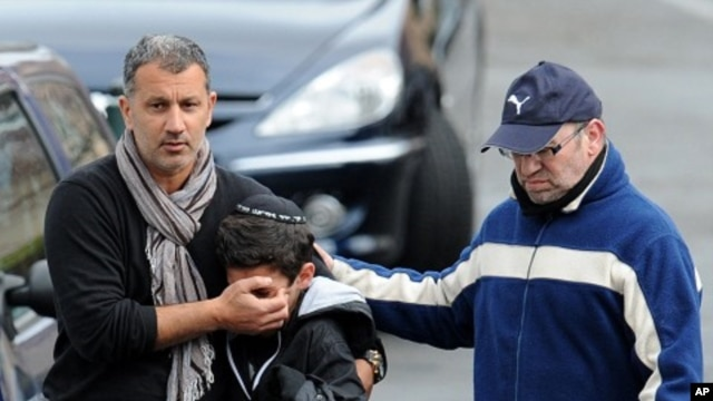 "Adults comfort a boy as they walk away from the ""Ozar Hatorah"" Jewish school in Toulouse, southwestern France, March 19, 2012"