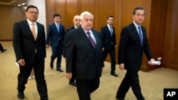 Syrian Foreign Minister Walid Moallem, center, and his Chinese counterpart Wang Yi, right, arrive for a press briefing at China's Ministry of Foreign Affairs in Beijing, Thursday, Dec. 24, 2015.