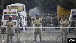 Pasukan keamanan Mesir berlindung di balik pagar berduri mengamankan kantor-kantor pemerintah dekat Lapangan Tahrir, Kairo (26/11).