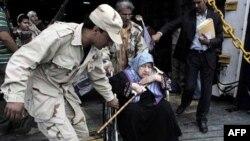Một chiến binh phe nổi dậy đang giúp đỡ một cụ già ở Misrata xuống phà để chạy lánh nạn