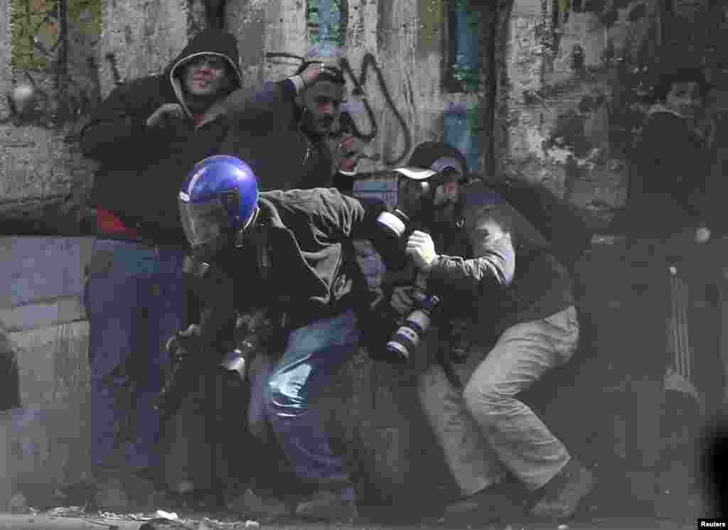 Photographers cower as protesters throw stones towards riot police near Tahrir Square, Cairo, Egypt, January 25, 2013.
