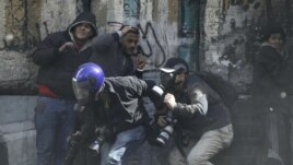Fotoreporteri se zaklanjaju od kamenica koje su demonstranti u Kairu danas bacali na policiju