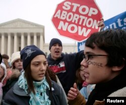 FILE - A pro-choice supporter is confronted by anti-abortion demonstrators in front of the U.S. Supreme Court in Washington January 22, 2007.