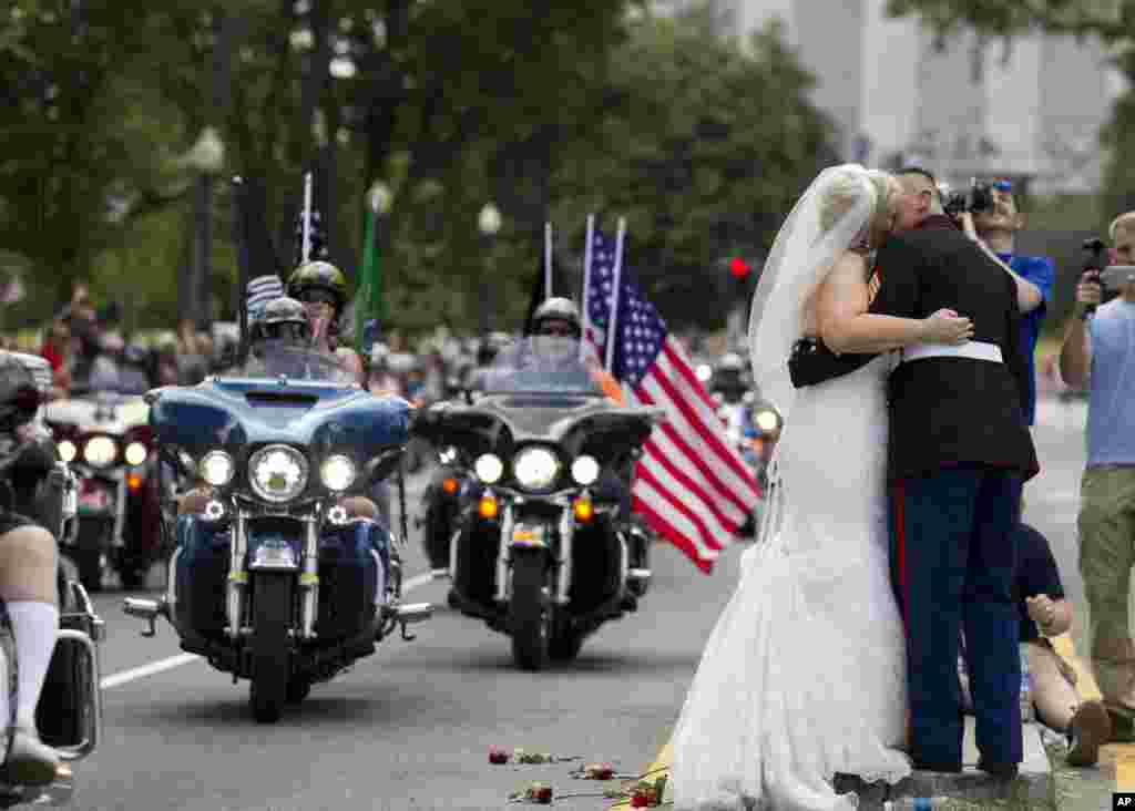 Hai vợ chồng mới cưới Tim Chambers, một Thủy quân lục chiến Mỹ, và Lorraine Heist hôn nhau khi những chiếc xe môtô chạy ngang qua trong cuộc diễu hành Rolling Thunder hàng năm tại thủ đô Washington, Mỹ, ngày 29 tháng 5, 2016.