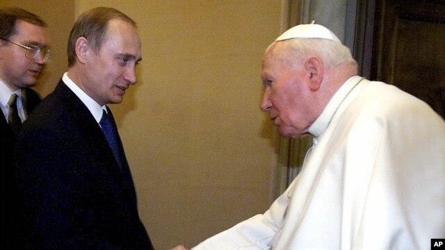 Pope John Paul II and Russian President Vladimir Putin shake hands at the Vatican, June 5, 2000.