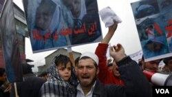Seorang pria Afghanistan dan anak laki-lakinya ikut serta dalam aksi protes anti-Amerika di Kabul, Minggu (6/3).