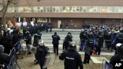 Полицијата меѓу поддржувачите на владата (лево) и на опозицијата (десно) за време на собраниските настани во Македонија на 24-ти декември 2012-та
