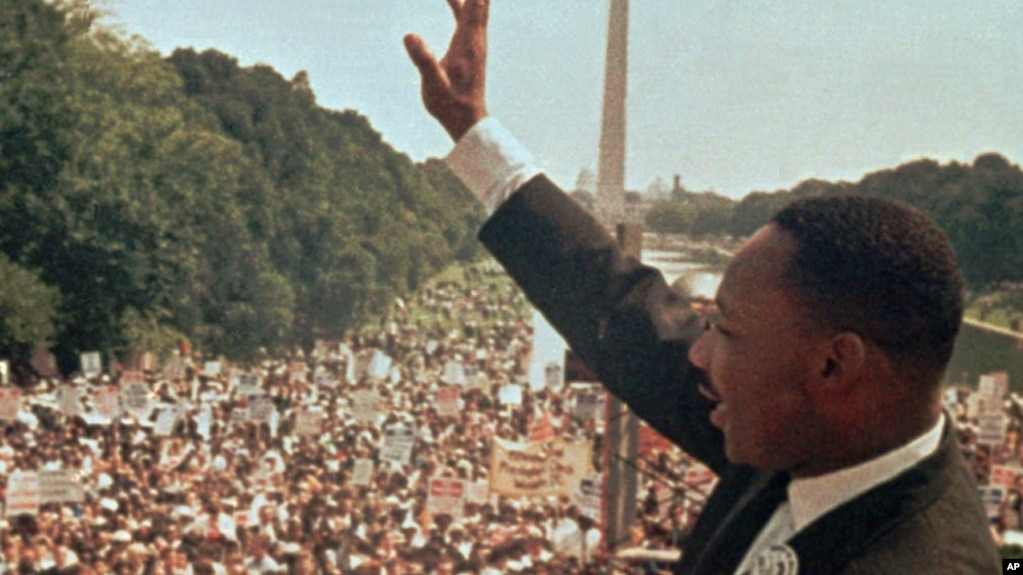 "Martin Luther King Jr. acknowledges the crowd at the Lincoln Memorial for his ""I Have a Dream"" speech during the March on Washington, Aug. 28, 1963."