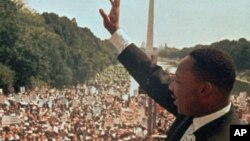 "Martin Luther King Jr. acknowledges the crowd at the Lincoln Memorial for his ""I Have a Dream"" speech during the March on Washington, August 28, 1963."