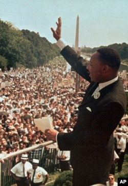 Martin Lyuter King Vashingtondagi nutq ketidan ommani olqishlamoqda, 28-avgust, 1963