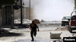 A man runs for cover during clashes between Free Syrian Army fighters and Syrian Army soldiers in the Salah al-Din neighborhood of central Aleppo August 4, 2012.