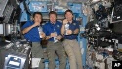 Японец Коичи Ваката, россиянин Геннадий Падалка и американец Майк Бэррэтт пробуют воду из нового опреснителя воды на борту МКС. 20 мая 2009 г.
