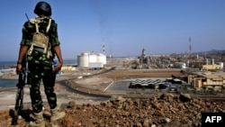 A Yemeni soldier is seen standing guard at the natural gas plant in Balhaf in this November 7, 2009, file photo.
