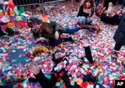 Revelers throw confetti on themselves after after celebrating the new year in Times Square, Sunday, Jan. 1, 2017, in New York.
