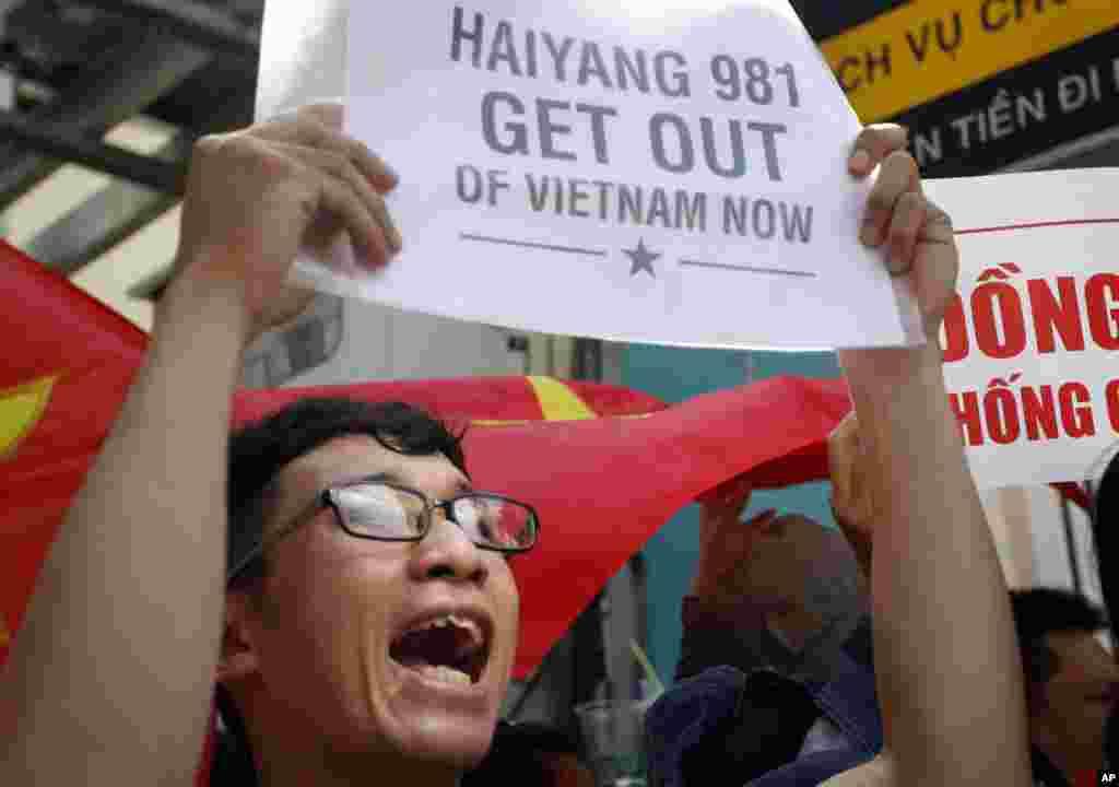 Người biểu tình Việt giương biểu ngữ và hô khẩu hiệu chống Trung Quốc trong cuộc biểu tình bên ngoài Lãnh sự quán Trung Quốc tại thành phố HCM.