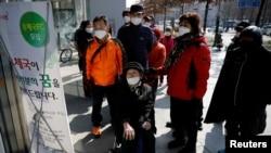 南韓新冠病毒確診病例不斷攀升,重災區大邱市民眾閱讀有關郵局販賣口罩的說明(2020年3月5日)