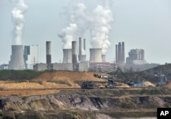 FILE - Machines dig for brown coal in front of a smoking power plant near the city of Grevenbroich in Germany.