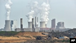 Machines dig for brown coal in front of a smoking power plant near the city of Grevenbroich in Germany. The Paris Agreement, which formally starts November 4, 2016, seeks to wean the world economy off fossil fuels.