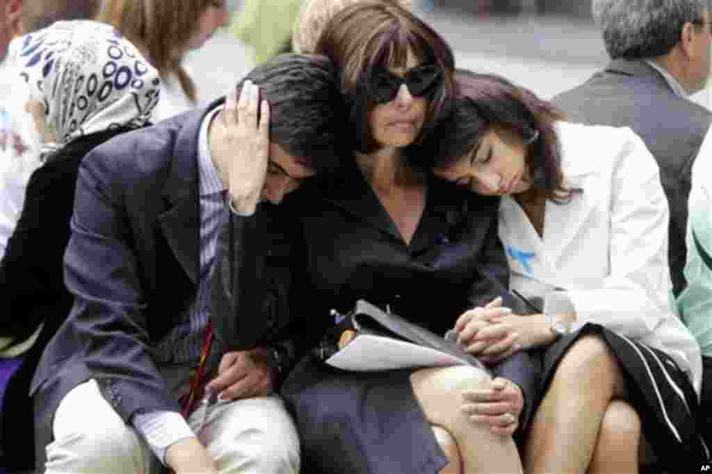 Alicia Bergstein, center, comforts her children Devin Bergstein, left, and Adrianna Bergstein while visiting the National September 11 Memorial at the World Trade Center site in New York, Sunday, Sept. 11, 2011. Daniel Bergstein, Alicia husband and the ch