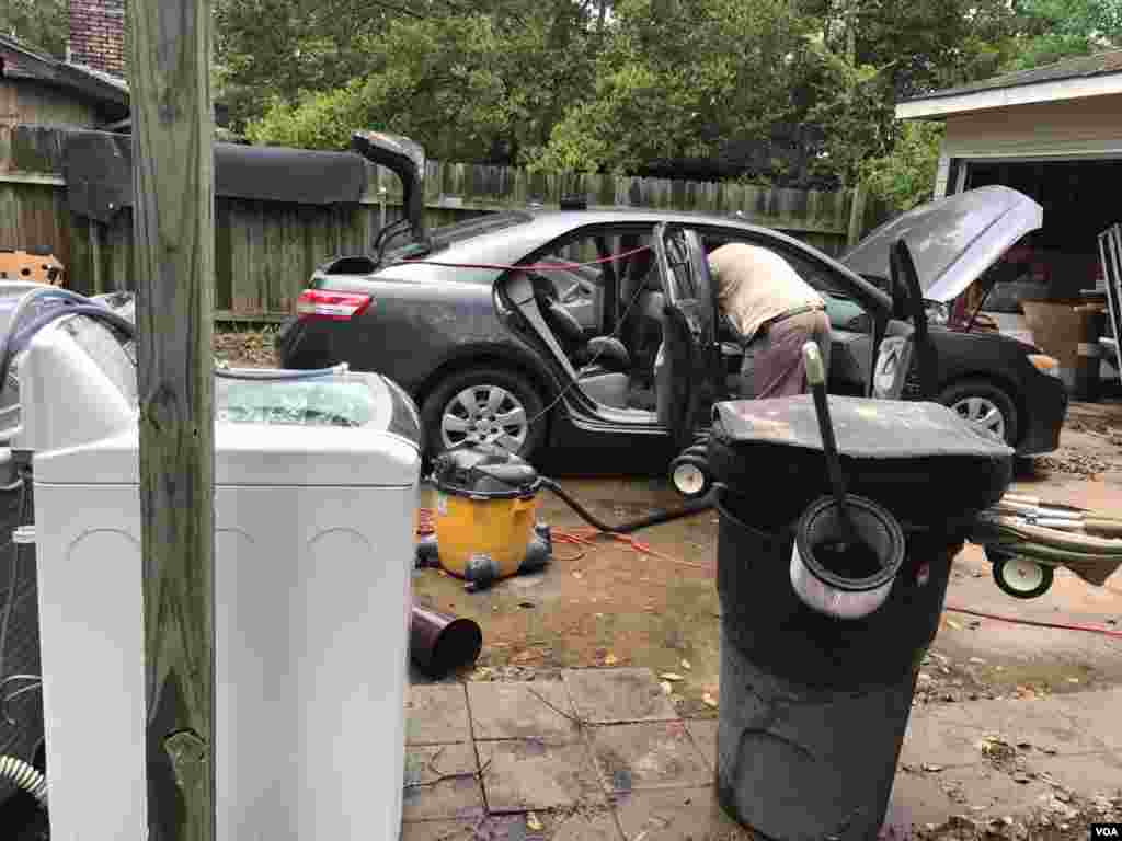 Residente en Houston limpia su auto una vez que las aguas de la inundación causada por la tormenta tropical Harvey comenzaron a bajar.