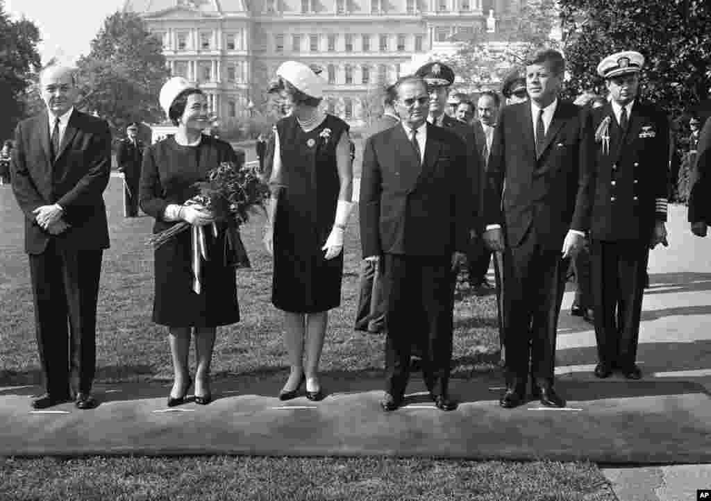 President John F. Kennedy and President Josip Broz Tito of Yugoslavia pose at the White House as Eunice Shriver, Kennedy's sister, chats with Tito's wife Jovanka, Oct. 17, 1963 in Washington. (AP Photo)