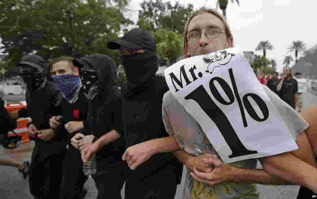 """Manifestantes que protestan contra la convención republicana de Tampa, se refieren a los delegados como """"señor 1%""""."""