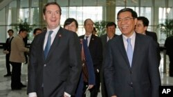 Britain's Chancellor of the Exchequer George Osborne (l) and Industrial and Commercial Bank of China Ltd (ICBC) Chairman Jiang Jianqing during his visit to the ICBC headquarters in Beijing, Oct. 15, 2013.