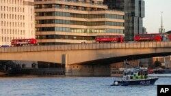 一艘英国警方船只从泰晤士河上向伦敦桥驶去。枪击事件发生后伦敦桥上停放着被丢弃的公共汽车。(2019年11月29日)