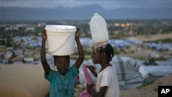 Haitian girls carry water to their family's tent at the Caradeux Camp in Port-au-Prince