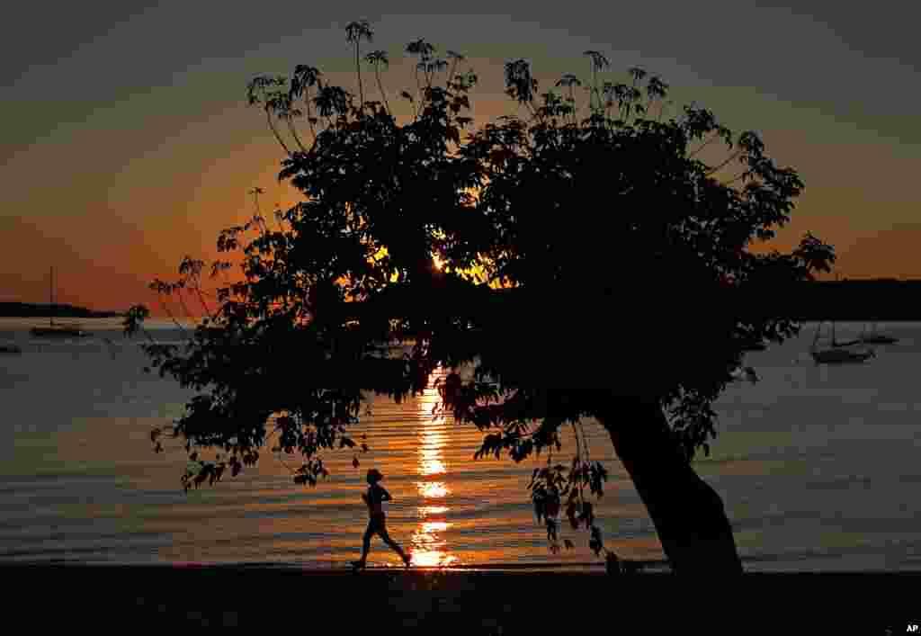 ស្រ្តីម្នាក់កំពុងរត់ហាត់ប្រាណនៅពេលព្រឹកព្រលឹមតាមឆ្នេរសមុទ្រ Willard Beach ភាគខាងត្បូង ប្រទេសប៉ូឡូញ រដ្ឋ Maine។