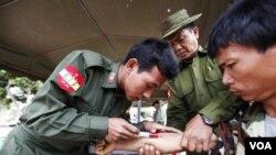 Seorang tentara Burma menyuntikkan obat-obatan kepada korban gempa di Minelin, MInggu (27/3).